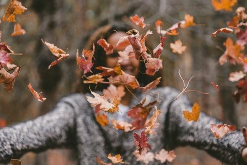 осенние идеи фото для инстаграм - девушка подбрасывает листья в лесу