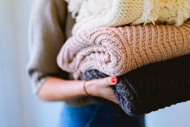 идеи фото осенью для инстаграм - девушка со сложенными свитерами в руках